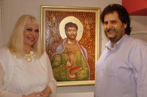 """Η Αγιογράφος με τον σύζυγό της επίσης διακεκριμένο θεωρητικό ιστορικό τέχνης Λεόντιο Πετμεζά κι ανάμεσά τους ο AΓΙΟΣ ΛΕΟΝΤΙΟΣ Αγιογραφία της Μαριλένας Φωκά που θα εκτεθεί στην ατομική της έκθεση με τίτλο """"EN TOYTΩ NIKA (IN HOC SIGNO VINCES)"""" στο Μουσείο Εθνικής Αντίστασης Ηλιούπολης."""